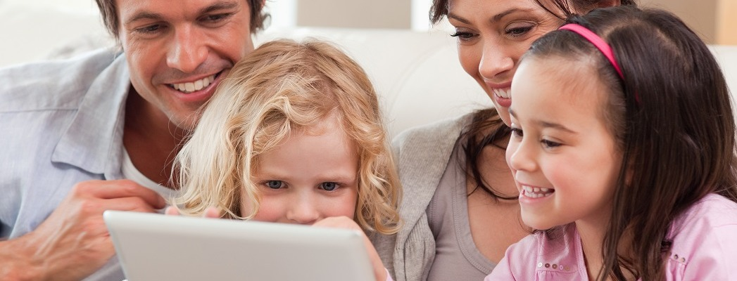 Delighted family using a tablet computer in a living room
