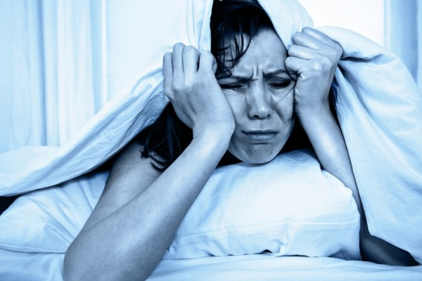 young moody woman in bed suffering stress with her insomnia problem and sleeping disorder or hangover covering with blanket and bedclothes on studio blue lighting